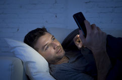 Young man in bed couch at home late at night texting on mobile phone in low light relaxed. In communication technology and internet social network concept royalty free stock images