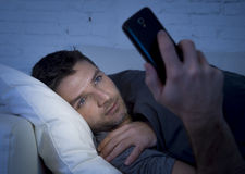 Young man in bed couch at home late at night using mobile phone in low light relaxed in communication technology concept. Young man in bed couch at home late at stock photo