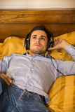 Young man in bed listening to music with headphones Royalty Free Stock Image