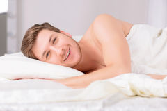 Young man in bed lying on the side Royalty Free Stock Photos