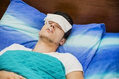 Young man in bed measuring fever with thermometer Royalty Free Stock Photo