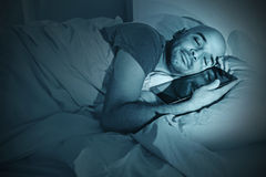 Young man in bed at night sleeping happy together with digital tablet Stock Photo