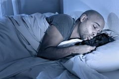 Young man in bed at night sleeping happy together with digital tablet Stock Photography