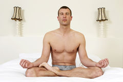 Young man on bed practicing yoga Royalty Free Stock Photos