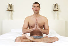 Young man on bed practicing yoga Royalty Free Stock Images