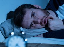 Young man in bed staring at alarm clock trying to sleep feeling stressed and sleepless. Sleepless and desperate young caucasian man awake at night not able to stock image