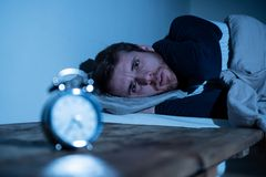 Young man in bed staring at alarm clock trying to sleep feeling stressed and sleepless. Sleepless and desperate young caucasian man awake at night not able to stock photos