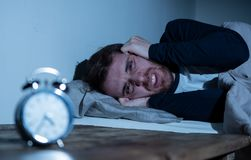 Young man in bed staring at alarm clock trying to sleep feeling stressed and sleepless. Sleepless and desperate young caucasian man awake at night not able to royalty free stock image