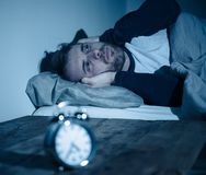 Young man in bed staring at alarm clock trying to sleep feeling stressed and sleepless. Sleepless and desperate young caucasian man awake at night not able to royalty free stock photo