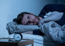 Young man in bed staring at alarm clock trying to sleep feeling stressed and sleepless. Sleepless and desperate young caucasian man awake at night not able to royalty free stock images