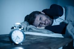 Young man in bed staring at alarm clock trying to sleep feeling stressed and sleepless. Sleepless and desperate young caucasian man awake at night not able to royalty free stock photography