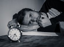 Young man in bed staring at alarm clock trying to sleep feeling stressed and sleepless. Sleepless and desperate young caucasian man awake at night not able to stock images
