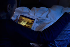 Young man in bed watching a movie or a series in his tablet stock photography