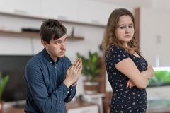 Young man is begging for forgiveness young angry woman at home. stock images