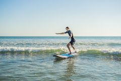 Young man, beginner Surfer learns to surf on a sea foam on the B. Ali island Stock Photos