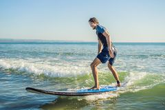 Young man, beginner Surfer learns to surf on a sea foam on the B. Ali island Stock Photo