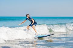 Young man, beginner Surfer learns to surf on a sea foam on the B. Ali island Royalty Free Stock Images