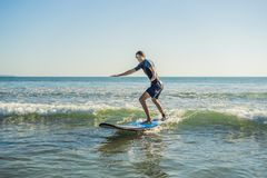 Young man, beginner Surfer learns to surf on a sea foam on the B. Ali island Royalty Free Stock Photo