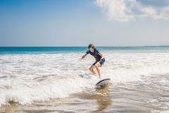 Young man, beginner Surfer learns to surf on a sea foam on the B. Ali island stock photography