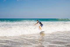 Young man, beginner Surfer learns to surf on a sea foam on the B. Ali island royalty free stock photography