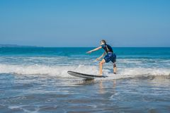 Young man, beginner Surfer learns to surf on a sea foam on the Bali island royalty free stock photography