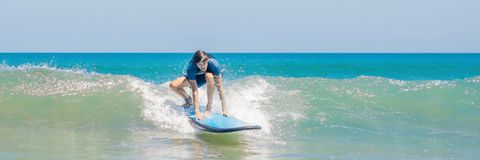 Young man, beginner Surfer learns to surf on a sea foam on the Bali island BANNER, long format. Young man, beginner Surfer learns to surf on a sea foam on the Royalty Free Stock Images