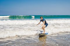 Young man, beginner Surfer learns to surf on a sea foam on the B royalty free stock images