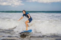 Young man, beginner Surfer learns to surf on a sea foam on the B. Ali island stock image