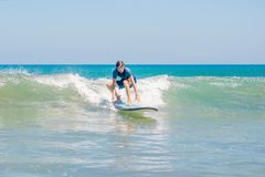 Young man, beginner Surfer learns to surf on a sea foam on the Bali island.  royalty free stock images