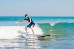 Young man, beginner Surfer learns to surf on a sea foam on the Bali island.  royalty free stock photography