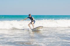 Young man, beginner Surfer learns to surf on a sea foam on the Bali island royalty free stock photos