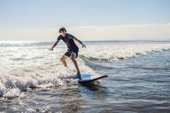 Young man, beginner Surfer learns to surf on a sea foam on the Bali island royalty free stock photo