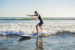 Young man, beginner Surfer learns to surf on a sea foam on the Bali island.  royalty free stock photos