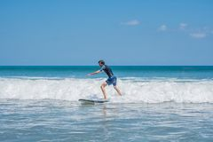 Young man, beginner Surfer learns to surf on a sea foam on the Bali island stock photography