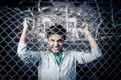 A young man behind bars close Royalty Free Stock Photo