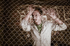 A young man behind bars close Royalty Free Stock Photography