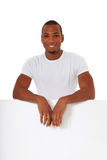 Young man behind blank white sign Royalty Free Stock Photography