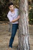 Young man behind a tree Stock Photos