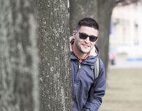 Young man behind tree Royalty Free Stock Photography