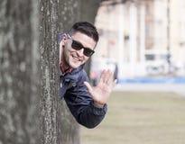 Young man behind tree Stock Photos