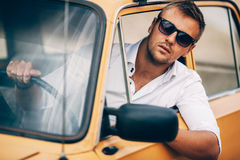 The young man behind the wheel of a beautiful appearance retro car. The young man behind the wheel of the beautiful appearance of the car retro yellow stock photography