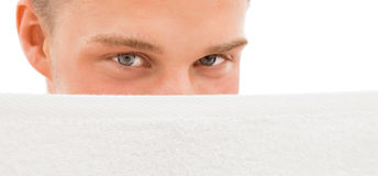 Young man behind white towel Royalty Free Stock Photography