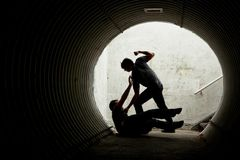 Young man being mugged in a dark tunnel. By a violent man Royalty Free Stock Photo