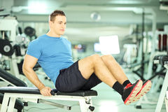 Young man on a bench exercising abdominal abs in a fitness club Stock Photos