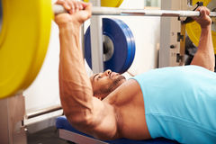 Young man bench pressing weights at a gym, side view close-up Royalty Free Stock Image