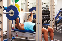 Young man bench pressing weights at a gym, side view Stock Photo