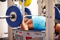 Young man bench pressing weights at a gym, side view Royalty Free Stock Photo