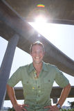 Young man beneath overpass, hands on hips, portrait (lens flare) Royalty Free Stock Images