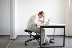 Young man is bent over his tablet.Bad sitting posture at work Stock Photos