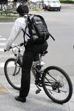 Young man on a bicycle. Young man with headphones and backpack riding a bicycle in a city Stock Images